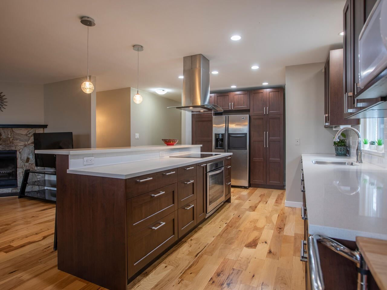 Open concept kitchen with huge quartz island with loads of cupboards