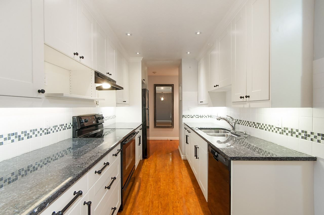 Crisp white shaker cabinets offer ample storage and black granite counters provide lots of working space for the chef.