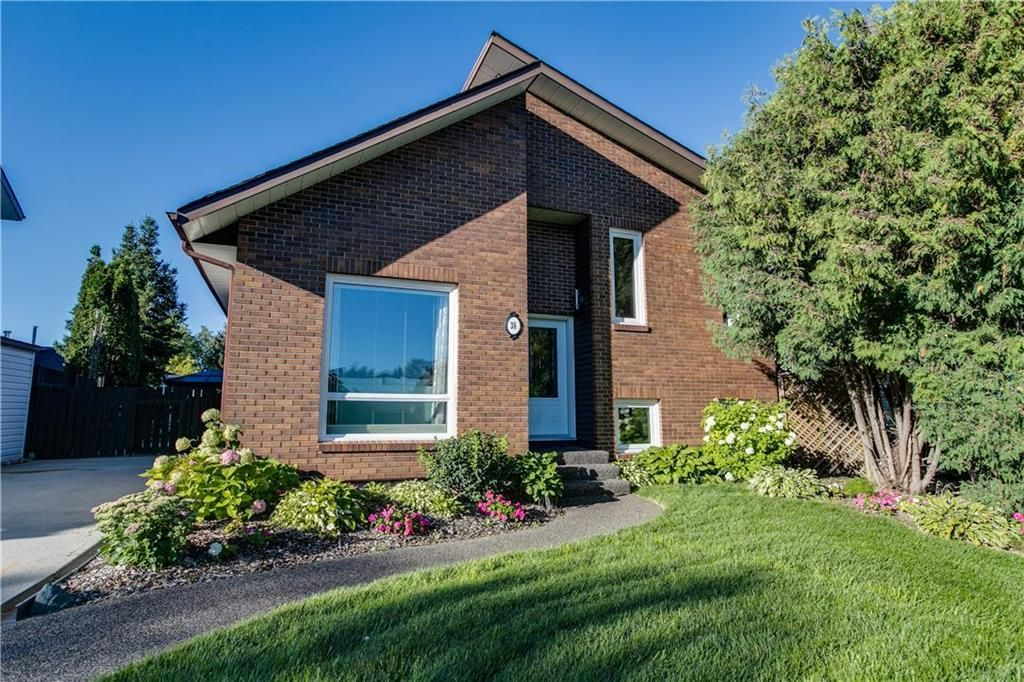 Beautiful perennial gardens and rubber paving on the front sidewalk, steps and patio add to the curb appeal of this timeless contemporary home.