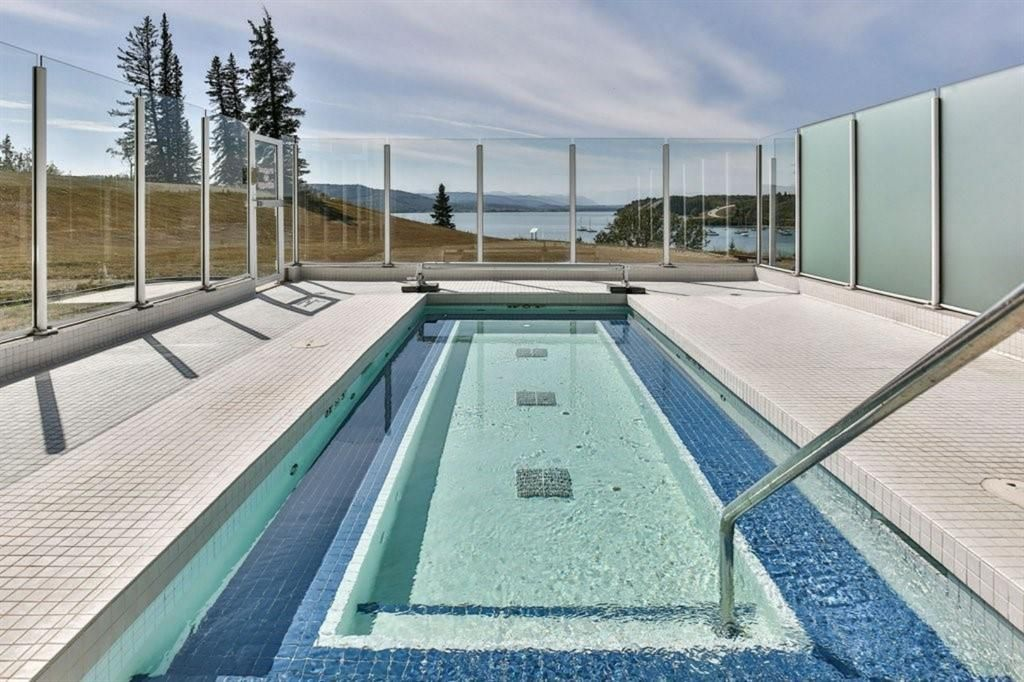 Spacious outdoor hot spa with mountain and lake views.