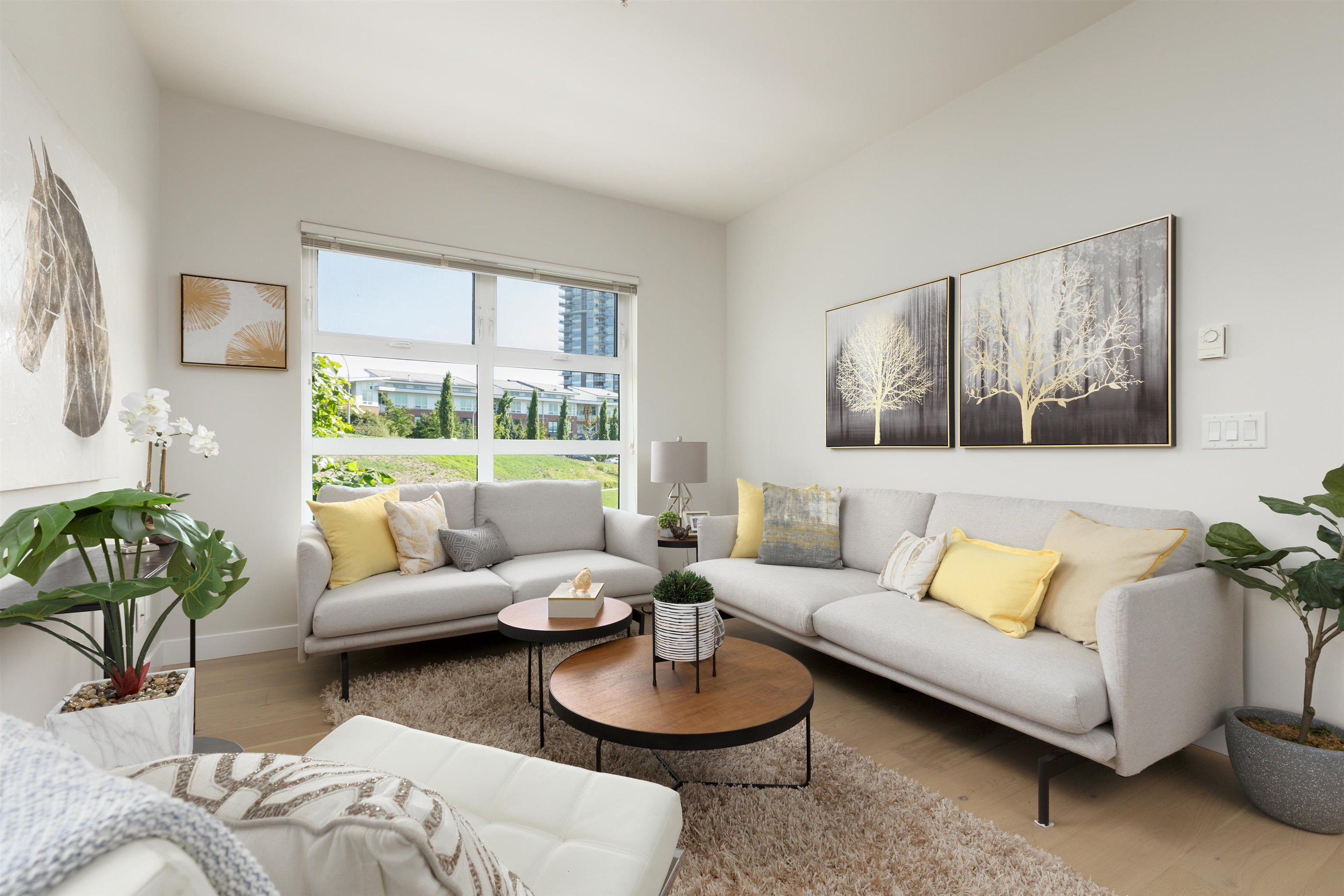 Enjoy the view of the neighboring park from the window in this spacious living room.