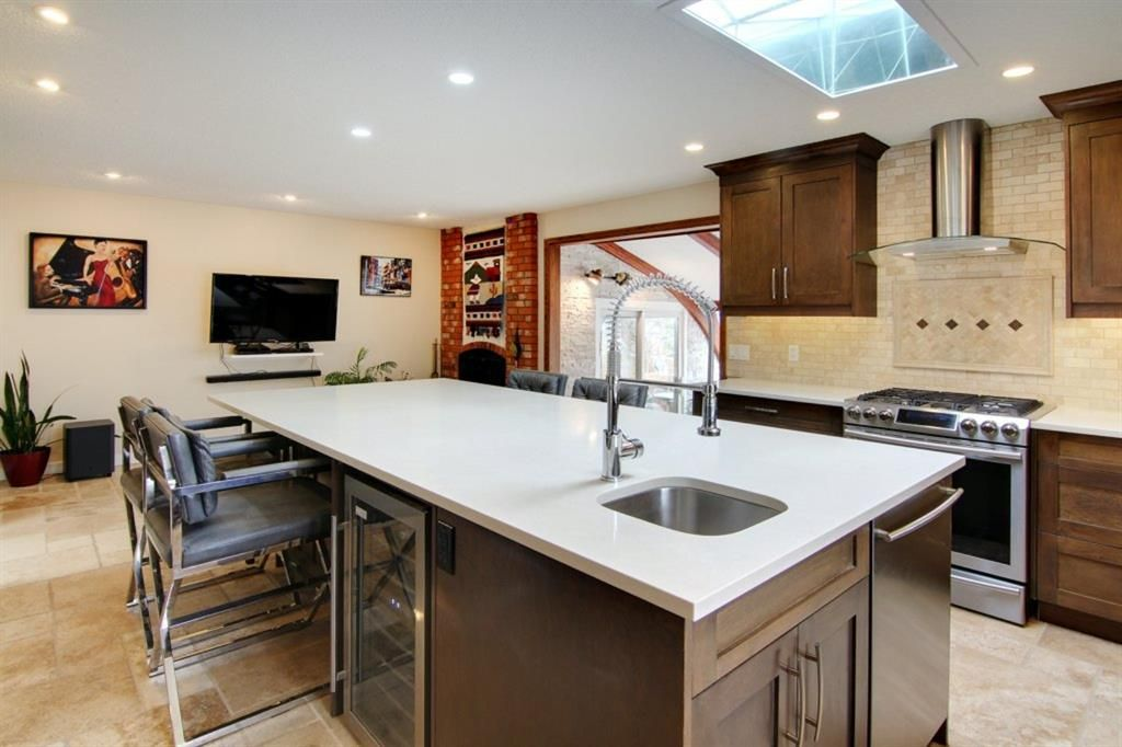 Fully renovated kitchen with quartz counters and travertine flooring.