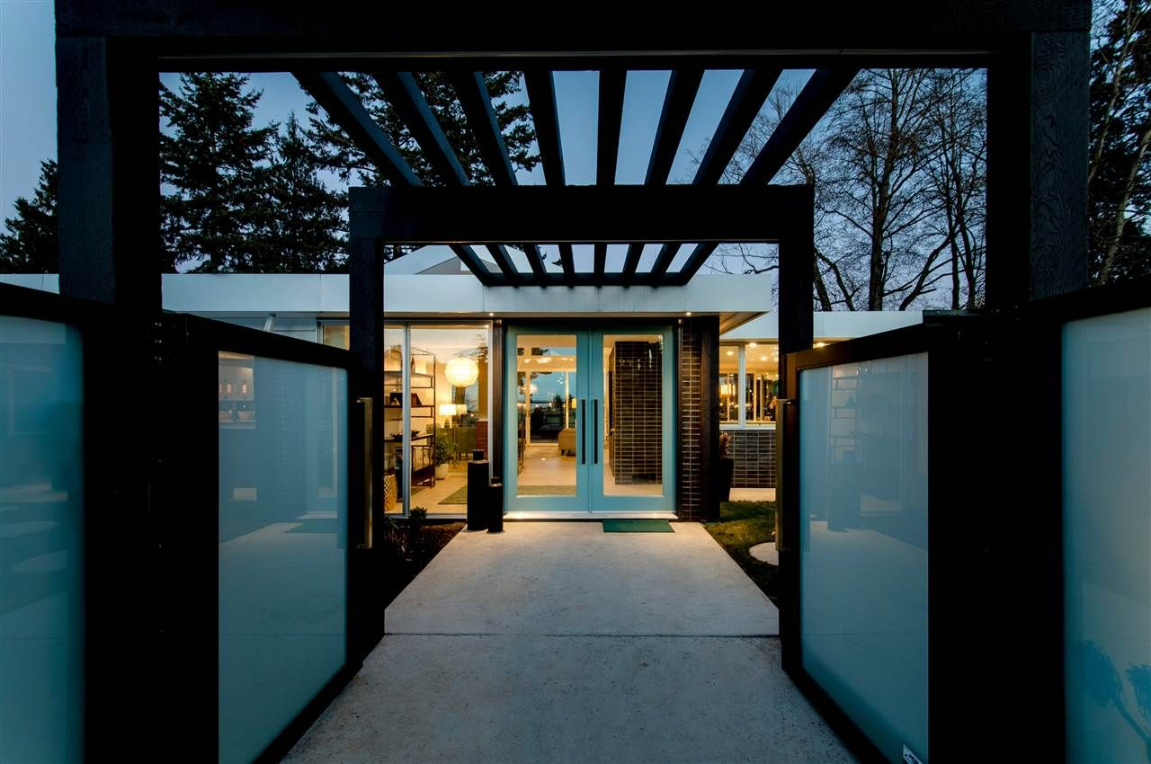 Linear pergola that draws your eye to the fabulous entrance doors.