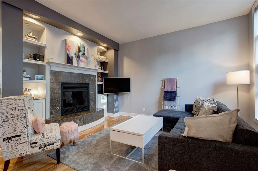 Gorgeous living room with marble-surround wood-burning fireplace (easily converts to gas), high ceilings hardwood floors and custom built-ins
