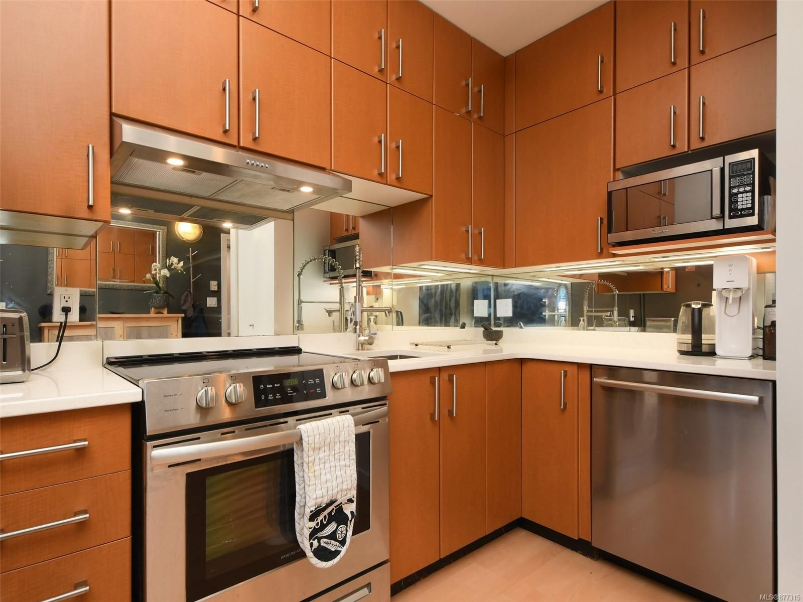 New Quart counters and high end Stainless Steel appliances with mirrored backspash make this kitchen modern and bright