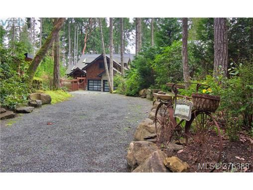 Charming stone flanked driveway leads to home.
