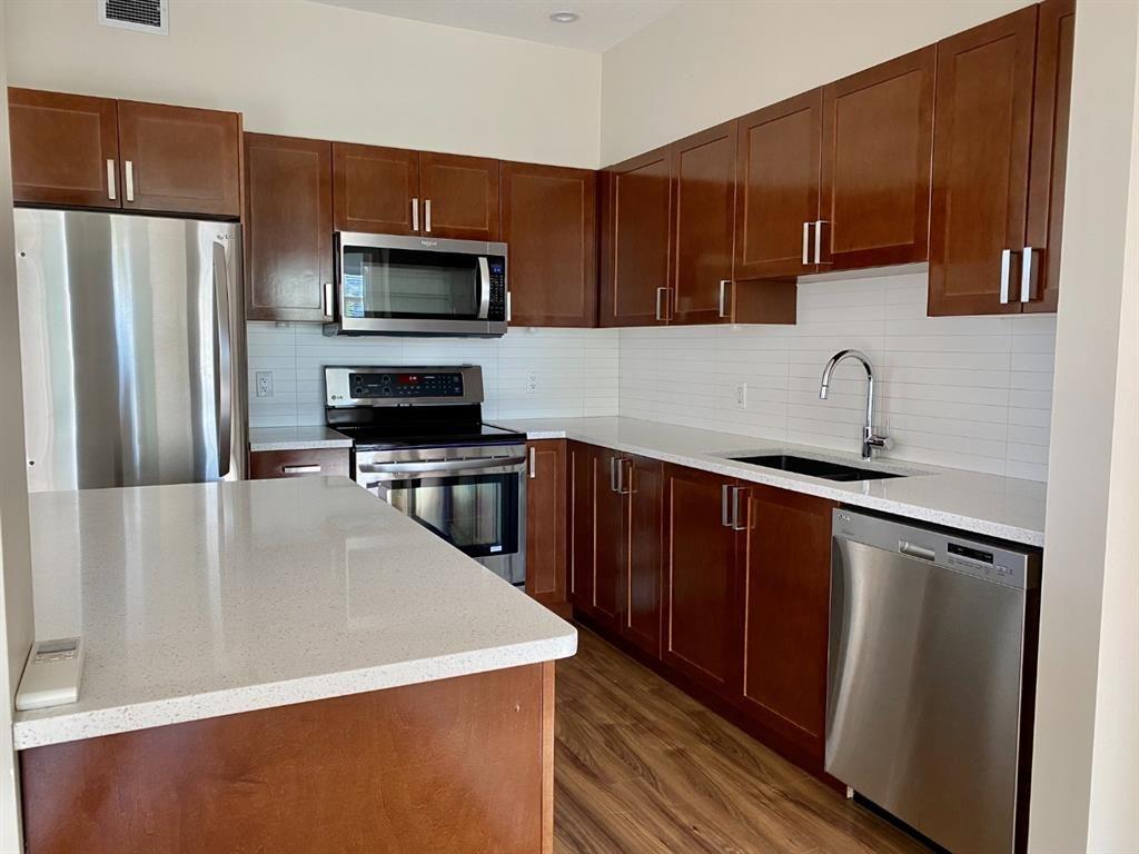 Rich dark kitchen cabinet with quartz countertops, under cabinet lighting, stainless steel appliances & eating bar