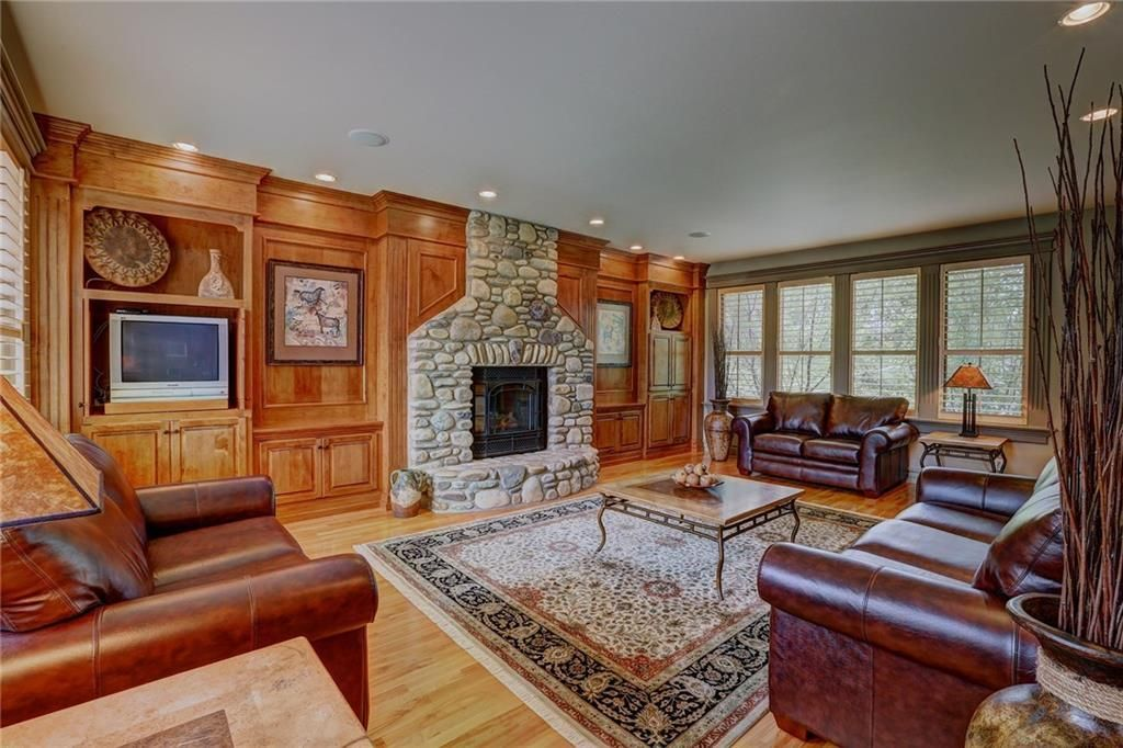 Great room with custom built-ins & river rock fireplace